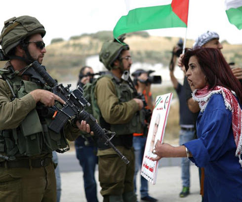 A Palestinian woman argue with Israeli soldiers during a protest in support of Palestinian prisoners on hunger strike in Israeli jails. (PA)