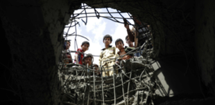 Boys look through a hole made by an air strike on a bridge in Sanaa, Yemen