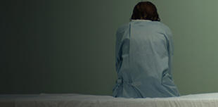 Female patient sitting alone on hospital bed