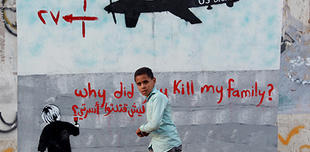 A boy in front of a drones mural in Yemen