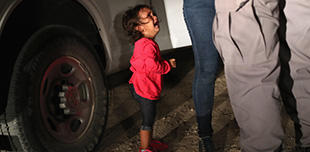 A two-year-old Honduran asylum seeker cries as her mother is searched and detained near the US-Mexico border on June 12, 2018