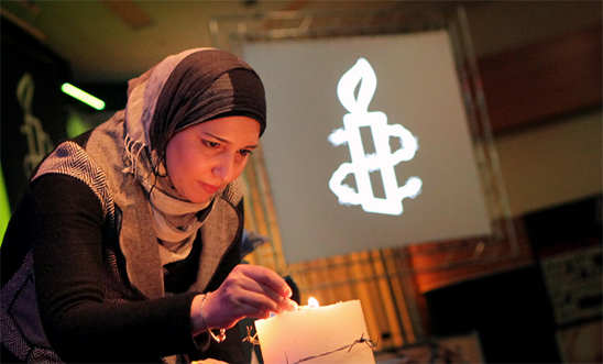 Reem Al Assil from the Syrian Non-Violence Movement lights the candle to open the AGM