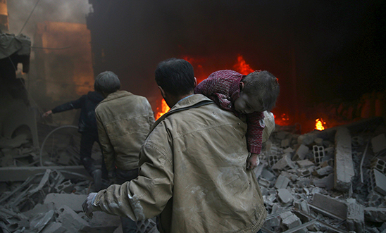 Man carries child after bombing in Douma, Syria