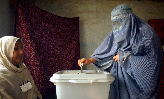 An Afghan woman wearing a burqa votes in Kabul 9/10/2004 Copyright: AP
